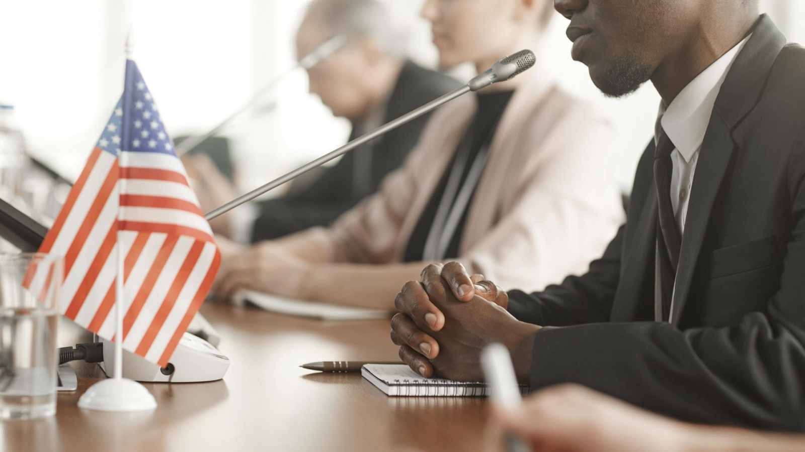 Man presenting at a group meeting with American flag on the table
