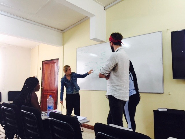 Photo: Fabiana, Ashyln, and Joel giving their presentation in class at NYU Accra.